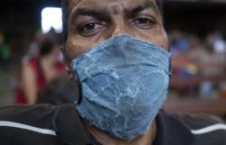 A man, wearing a weathered protective face mask as a precaution against the spread of the new coronavirus, waits to receive a free meal at a church in The Cemetery neighborhood of Caracas, Venezuela, Friday, May 22, 2020