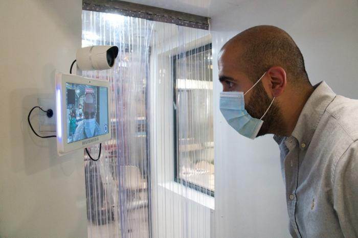 In this April 27, 2020, file, photo, a worker examines a gate system made by Guard ME that conducts temperature checks and fogs disinfectants on users, in Dubai, United Arab Emirates