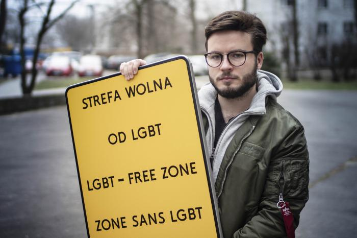 Bart Staszewski, an LGBT activist, holds up a sign he uses to protest anti-LGBT resolutions, in Warsaw, Poland.