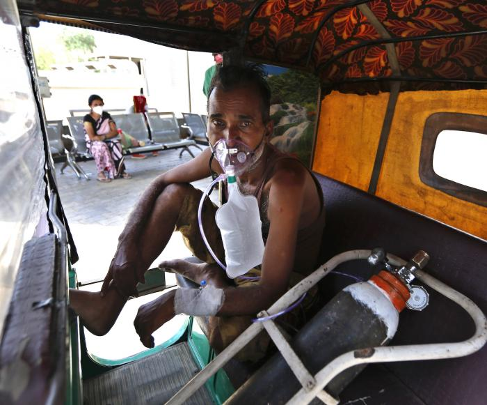 A COVID-19 patient breathes with the help of an oxygen mask as he waits inside an auto rickshaw to be attended to and admitted in a dedicated COVID-19 government hospital in Ahmedabad, India.