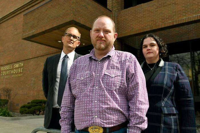 Randall Menges, front, along with his attorneys Matthew Strugar and Elizabeth Ehret, pause outside the Russell Smith Federal Courthouse in March, 2021, in Missoula, Mont.