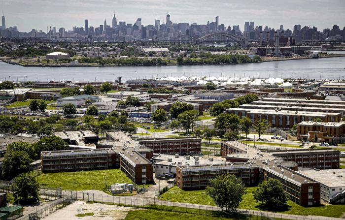 The Rikers Island jail complex in the foreground within the East River and the New York skyline in the background.